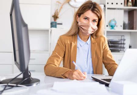 Photo pour Woman in disposable face mask working in office using laptop - image libre de droit
