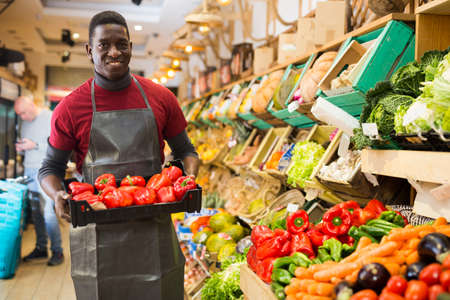 Photo pour Seller arranging red peppers on greengrocery counter - image libre de droit