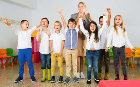 Photo for Portrait of cheerful female teacher with her happy schoolkids in classrom - Royalty Free Image