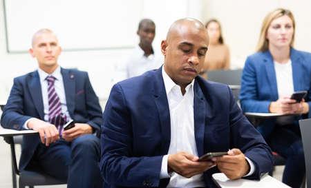 Foto de Corporate employees attentively listening to business training in conference room - Imagen libre de derechos