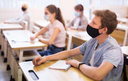 Photo pour Schoolboy wearing face mask working in class - image libre de droit