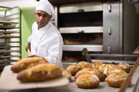 Foto für Male baker pulls hot bread out of the oven at bakery - Lizenzfreies Bild