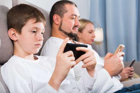 Foto de Modern family with smartphones at home - Imagen libre de derechos