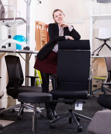 Photo pour Saleswoman standing in chair store - image libre de droit