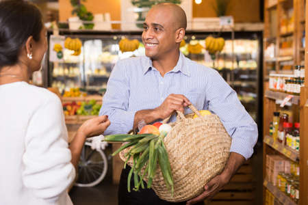Photo pour Smiling Latino with purchases talking to woman in grocery store - image libre de droit