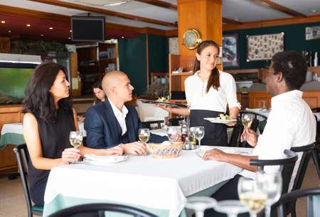 Photo pour Smiling waitress serving meals to guests in restaurant - image libre de droit