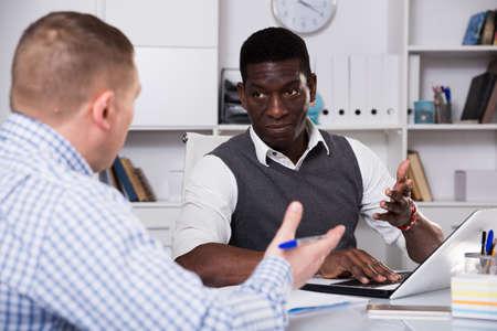 Photo pour Businessmen in office clothes filling up documents indoor - image libre de droit