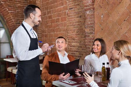 Photo pour Male waiter taking order from visitors - image libre de droit
