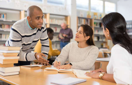 Photo for Latin American man with female friends studying in university library - Royalty Free Image