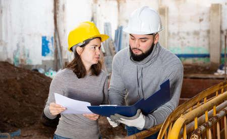 Photo pour Engineers discussing blueprint at construction site - image libre de droit