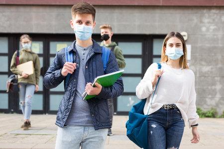 Photo pour Teenagers in masks walking after lessons - image libre de droit