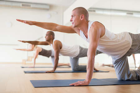 Photo for Man practicing Dandayamna Bharmanasana during group yoga training - Royalty Free Image