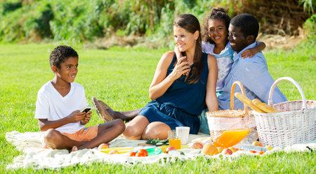 Photo pour Boy playing on smartphone during family picnic - image libre de droit