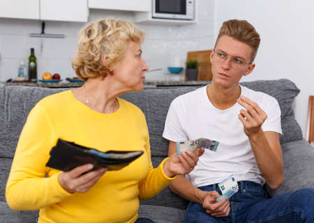 Photo for Mature woman giving pocket money son - Royalty Free Image