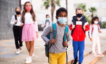 Photo pour Schoolboy in medical mask standing near school, kids on background - image libre de droit