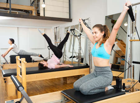 Photo for Young woman practicing pilates exercises on reformer at gym - Royalty Free Image