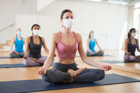 Photo pour Girl in protective mask sitting in lotus positions during group yoga training - image libre de droit