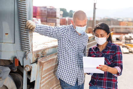 Photo pour Manager in protective mask gives instructions to the car driver at building materials storage site - image libre de droit