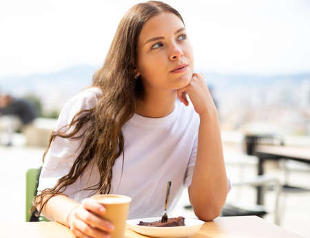 Photo for Portrait of a thoughtful girl sitting at a table with a cup of coffee - Royalty Free Image