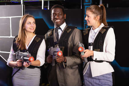 Photo for African man and young women holding laser guns - Royalty Free Image
