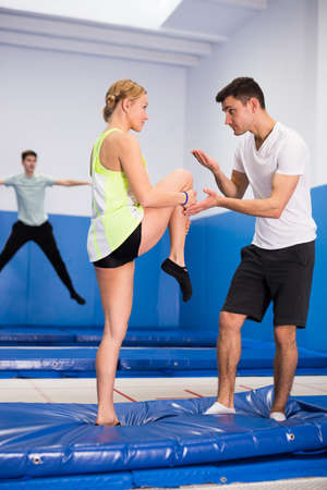 Photo for Instructor holding training with woman in trampoline room - Royalty Free Image