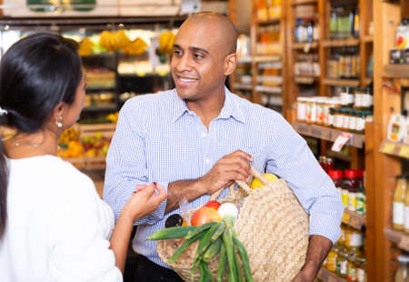 Photo pour Communication of a man and a woman in grocery supermarket - image libre de droit