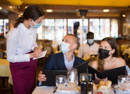 Photo pour Positive young couple making order at restaurant - image libre de droit