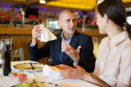 Photo pour Young couple man and woman quarreling in restaurant - image libre de droit