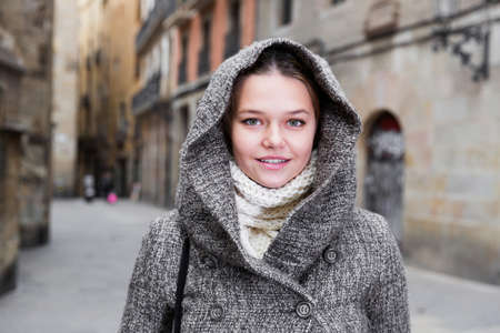 Photo pour young girl in coat hood at the old street - image libre de droit
