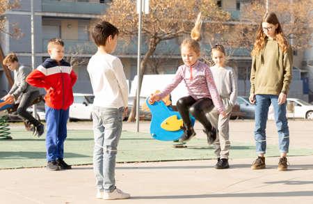 Photo pour Children skipping on elastic jump rope - image libre de droit