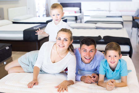 Photo pour parents with two young sons testing mattress in store - image libre de droit
