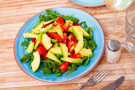 Photo pour Tasty salad with avocado, tomatoe and arugula at plate - image libre de droit