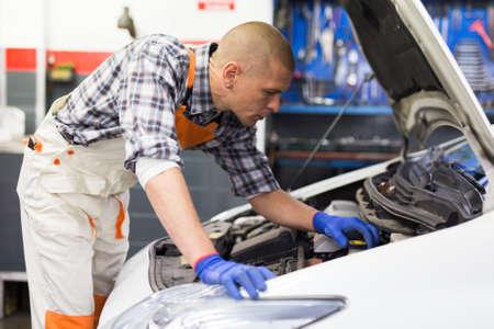 Photo pour Positive man car mechanician repairing car in auto repair service - image libre de droit