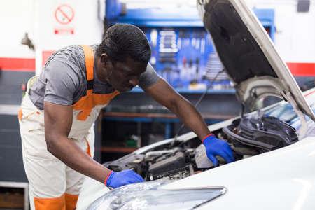 Photo for Professional american mechanic man in uniform repairing car engine - Royalty Free Image