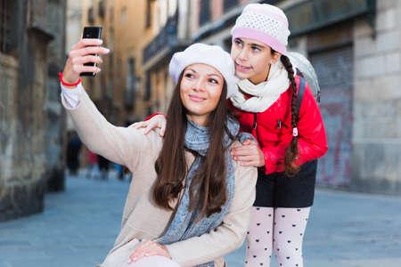Photo pour adult female and girl taking selfie - image libre de droit