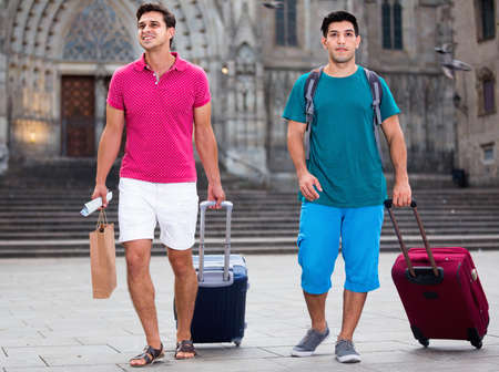 Photo for Men tourists are walking with suitcases in unknown city. - Royalty Free Image