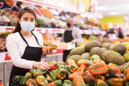 Photo pour Friendly woman seller in mask in supermarket - image libre de droit