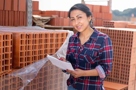 Photo pour Female worker checking quantity of red bricks in warehouse - image libre de droit
