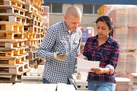 Photo pour Couple of wokers checking order at hardware store warehouse - image libre de droit