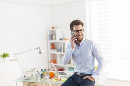 Foto de young man at phone at office - Imagen libre de derechos