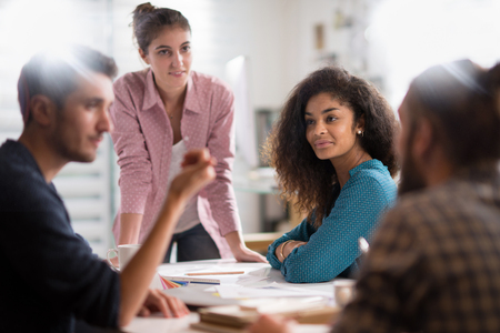 meeting at the company. A young woman leads a multi-ethnic gro
