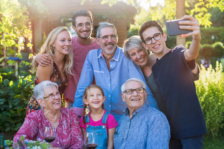 Photo pour during a bbq a teenager does a selfie with the whole family - image libre de droit