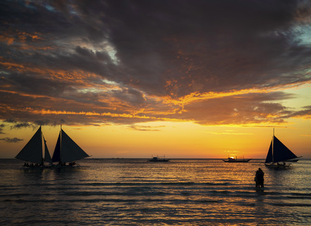 beautiful tropical sunset with sailing boats and tourists in boracay island philippines