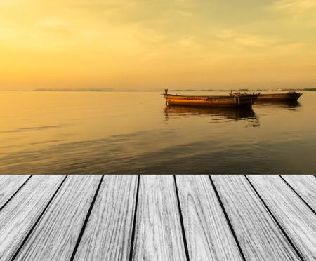 Foto de Wood Terrace on The Beach with Sunset and Big Boats - Imagen libre de derechos