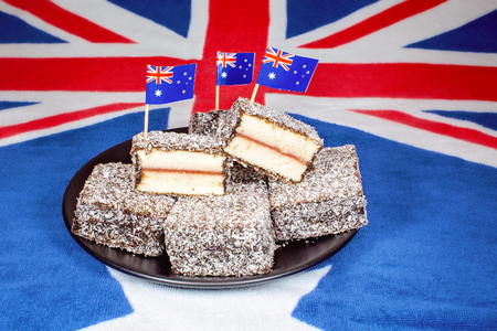 Foto de Australian lamingtons with tiny flags on toothpicks on a background of the country's flag - Imagen libre de derechos
