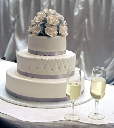 A white wedding cake with white icing rosesの写真素材