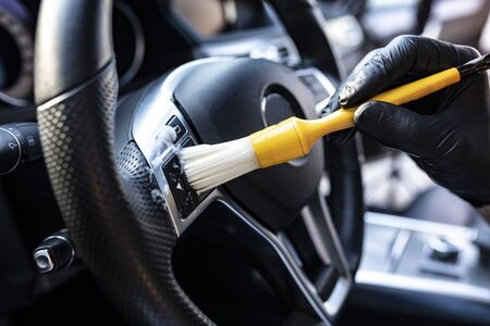 Photo pour The man vacuums the interior details of the car with a brush - image libre de droit