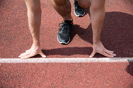 A starting position of a sprinter on a running track, close-up on hands and feet.