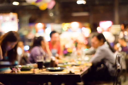 Photo for People enjoying dinner party background blur with bokeh - Royalty Free Image