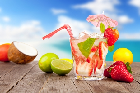 Foto für Strawberry mojito with pieces of fruit on wooden table. Blur beach on background - Lizenzfreies Bild